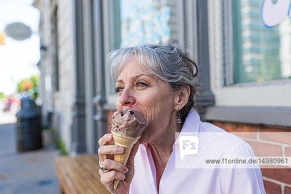 Ältere Frau sitzt auf dem Bürgersteig und isst Schokoeiswaffel
