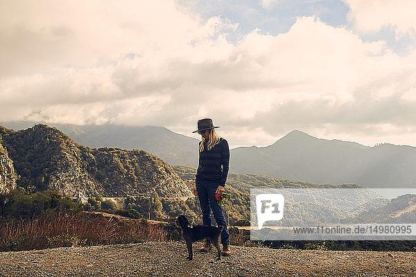 Woman walking dog on hilltop  Big Bear Lake  California  United States
