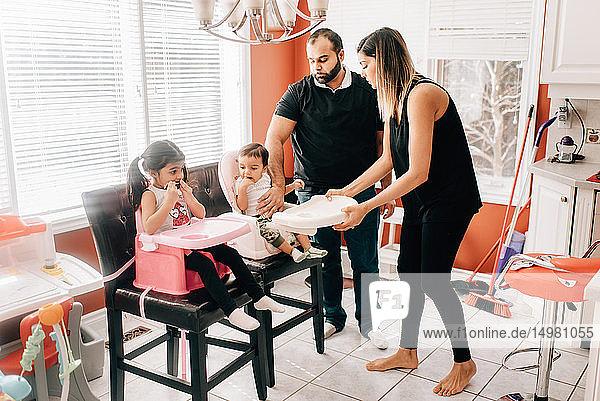 Paar mittlerer Erwachsener in der Küche mit Tochter und kleinem Sohn auf Hochstühlen