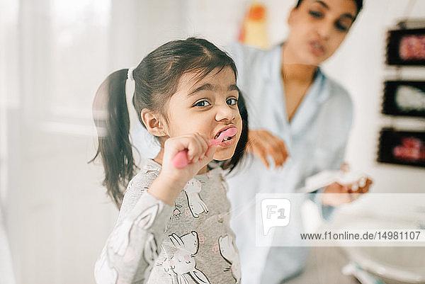 Mädchen mit Mutter beim Zähneputzen im Badezimmer
