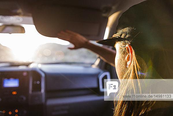Frau als Beifahrerin auf dem Vordersitz eines Autos  die die Augen vor Sonnenlicht schützt  Blick über die Schulter