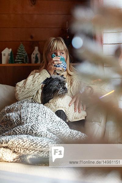 Frau trinkt und kuschelt Hund auf dem Sofa zu Hause