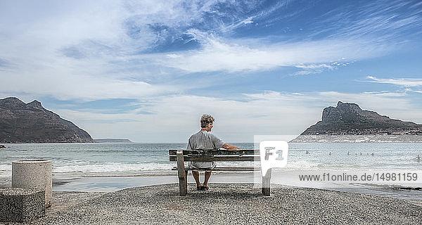 Älterer Mann sitzt auf einer Strandbank und schaut hinaus  Kapstadt  Western Cape  Südafrika