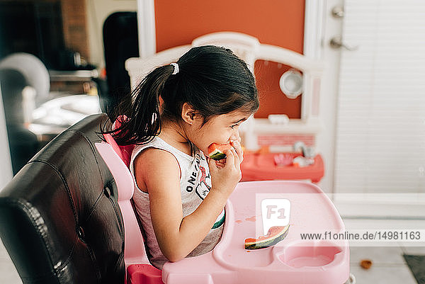 Girl in high chair eating water melon  side view
