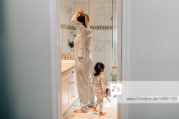 Girl and mother getting ready in bathroom
