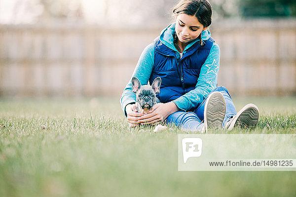 Mädchen spielt mit Welpe auf Rasen