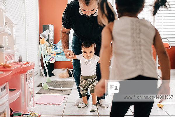 Mädchen vor dem gehenden Vater und dem kleinen Bruder in der Küche
