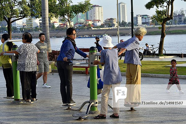 People do gym in the Mekong riverfront promenade in Phnom Penh Cambodia South east Asia.