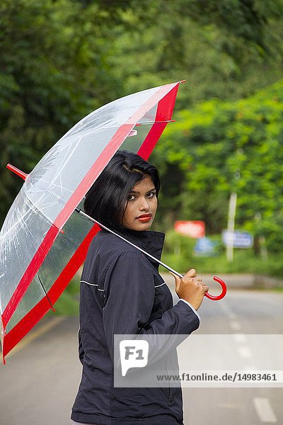 Young Indian girl with short hair holding a transparent umbrella and looking back  Pune.