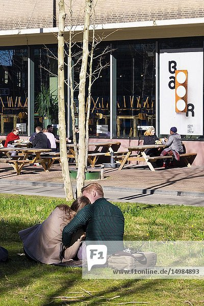 Couple chilling in the grass in front of the Veem building at Strijp-S  Eindhoven  the Netherlands.