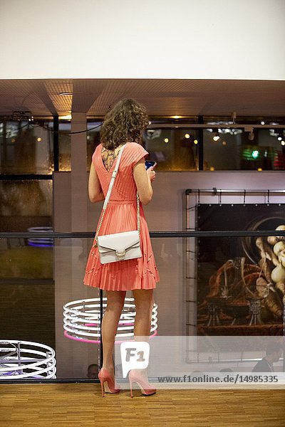 Lady dressed in pink on high heels checking her mobile phone.