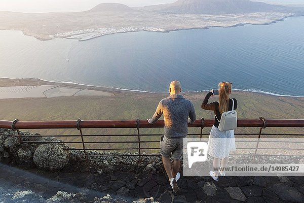 Young couple watching the abyss. Mirador del Rio  Lanzarote. Spain.