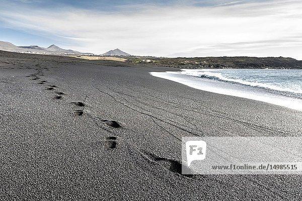 Footprints on the black sand of the Janubio beach. El Golfo  Lanzarote. Spain.