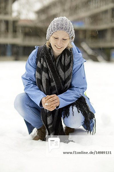 Woman crouching on snow in winter  in Munich  Germany.