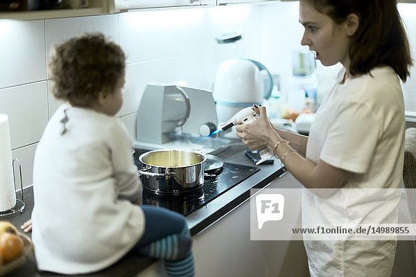 Mother and toddler preparing food in kitchen at home  using flambé  in Munich  Germany.
