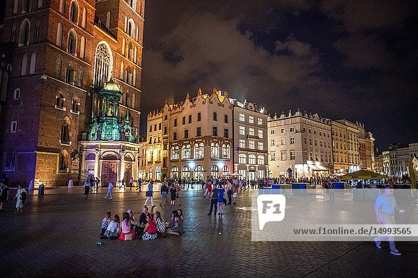 People walking and hanging out on the cobblestone streets of the Main Market Square of Krak—w Old Town at night  Lesser Poland Voivodeship  Poland.
