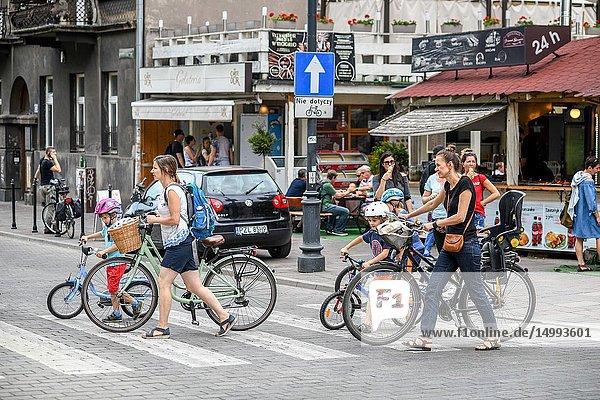 Mothers and their children walk with bikes in crosswalk in Kraków  Lesser Poland Voivodeship  Poland.