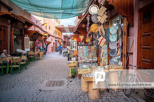 Market stalls selling handcrafted goods and souvenirs line either side of narrow street in medina quarter of Marrakesh  Morocco.