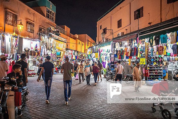 Shoppers walk the streets of medina quarter of Marrakesh at night and browse the of shops and market stalls selling textiles and other goods  Morocco.