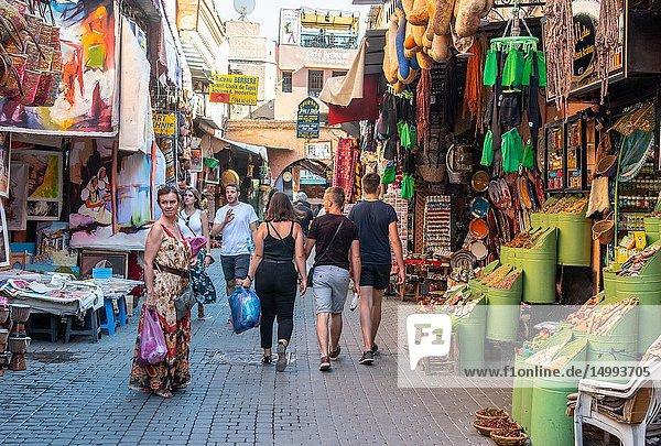 Shoppers wander down narrow street in medina quarter of Marrekech lined with market stalls selling art  spices  and other goods  Morocco.