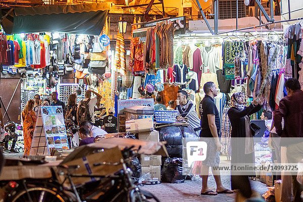 Market stalls crowded together sell a variety of goods to browsing shoppers in medina quarter of Marrekech  Morocco.