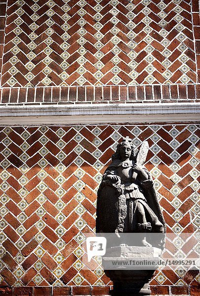 A sculpture of an angel holding a Feather and colored ceramic tiles decorate a Colonial House in Puebla  Mexico.