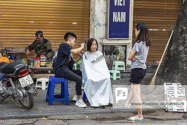 Woman having a haircut from a street hairdresser  Old Quarter  Hanoi  Vietnam  Asia.