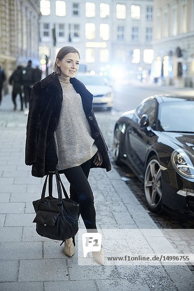Fashionable blogger woman at street in evening  in Munich  Germany.