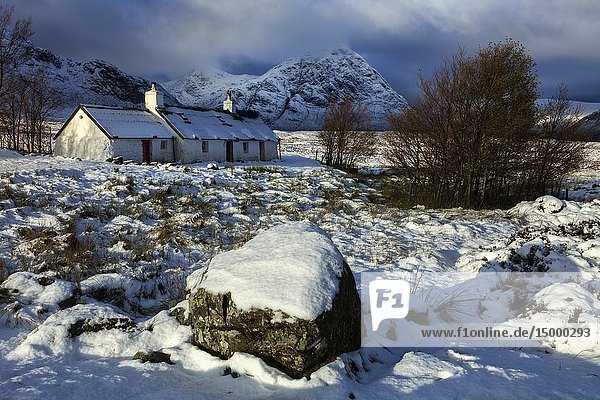 Black Rock Cottage on Rannoch Moor in the Scottish Highlands illuminated by the first rays of sunlight following an overnight snowfall in early November.