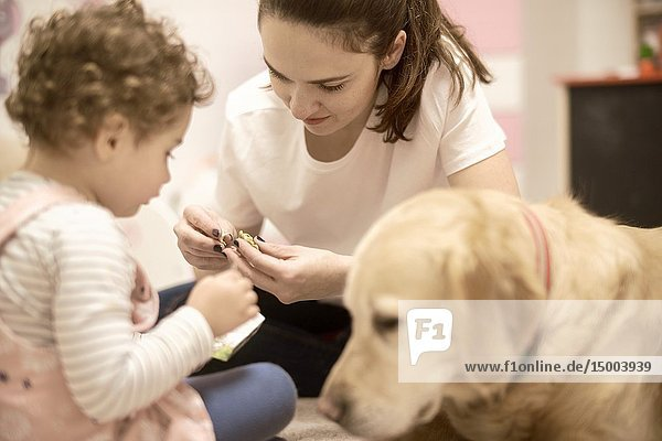 Woman with toddler and dog at home in childrens room  in Munich  Germany.