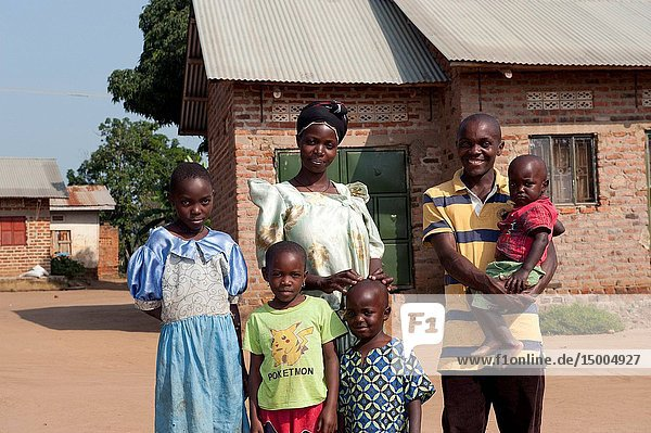 Prosperous looking Ugandan family in front of their rural home.