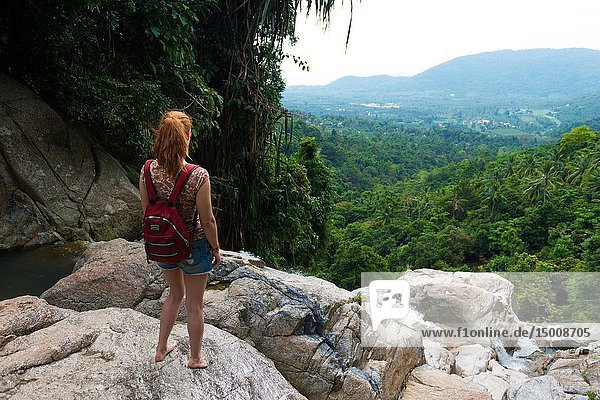 Girl standing on a cliff of Namuang waterfall  observing the nature of Samui island  Thailand.