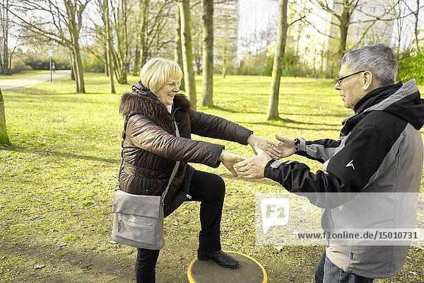 Senior man taking senior woman on hands in park  helping to balance  old couple  in Cottbus  Brandenburg  Germany.