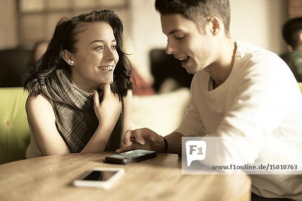 Happy woman looking at optimistic man using smartphone at table in café  Germany