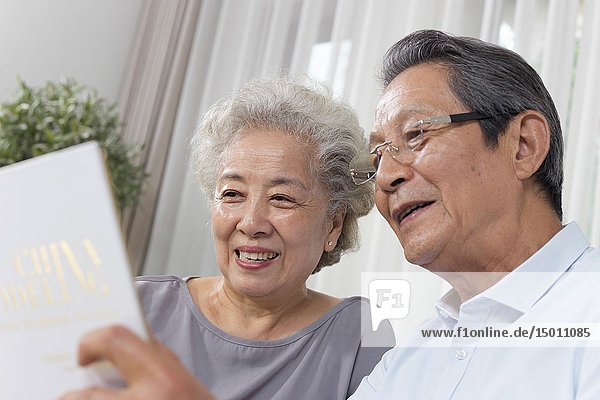 Elderly couple drinking looking at book