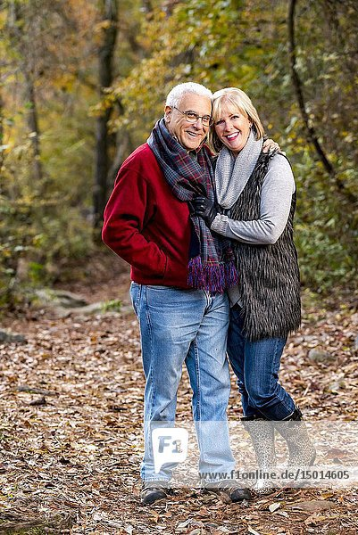 A happy 65 year old man and a 59 year old blond woman walking together in a forest setting.