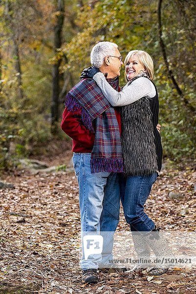 A happy 65 year old man and a 59 year old blond woman hugging and smiling at each other in a forest setting.