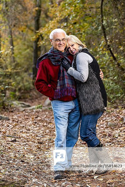 A happy 65 year old man and a 59 year old blond woman hugging in a forest setting looking at the camera.