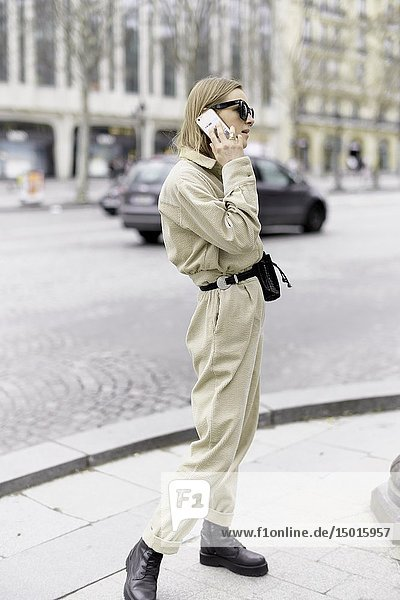 Fashionable woman calling with mobile phone at street during fashion week  in Paris  France.