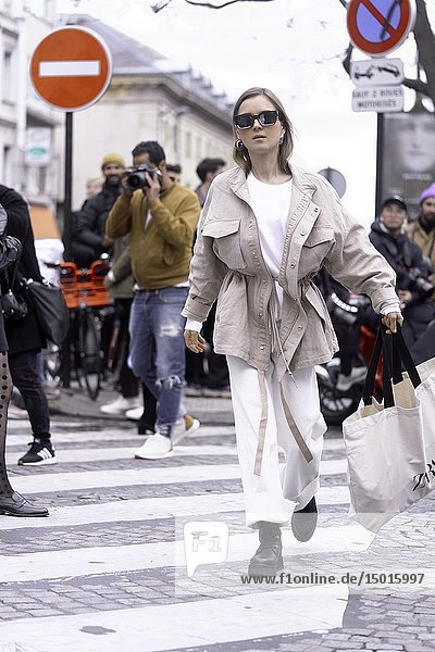 Fashionable woman crossing road at crosswalk during fashion week  in Paris  France.