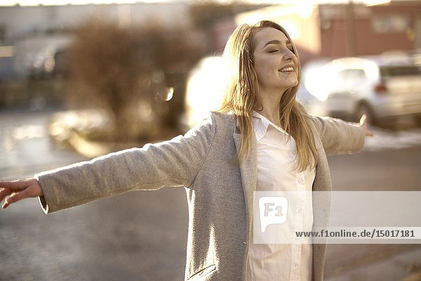 Young woman outdoors in sunlight at street in city  in Cottbus  Brandenburg  Germany