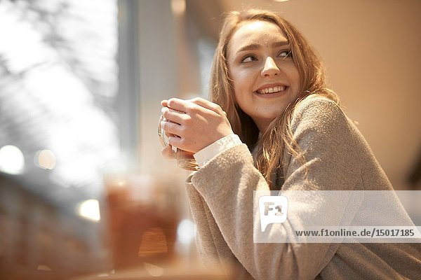 Young woman with warm tea in hands  indoors in café  in Cottbus  Brandenburg  Germany