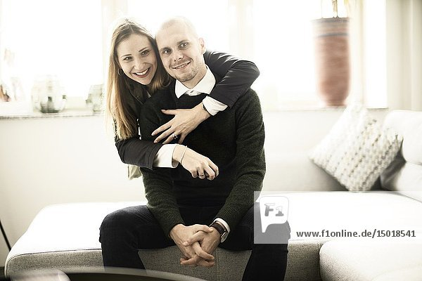 Couple at home  wife embracing husband from behind  in Cottbus  Brandenburg  Germany.