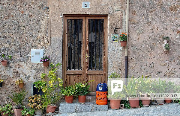 VALLDEMOSSA  MALLORCA  SPAIN - MARCH 21  2019: Flowers and butane gas bottle outside door in the old town on March 21  2019 in Valldemossa  Mallorca  Spain.