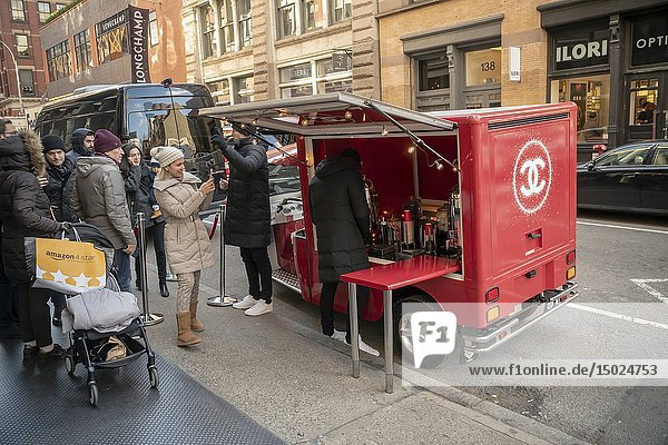 Chanel distributes free hot 'Coco' to shoppers outside their store in Soho in New York on Saturday  December 8  2018 during the Christmas shopping season. (© Richard B. Levine).