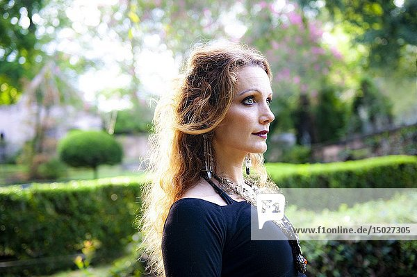 Profile of a 41 year old redhead woman in a garden setting.