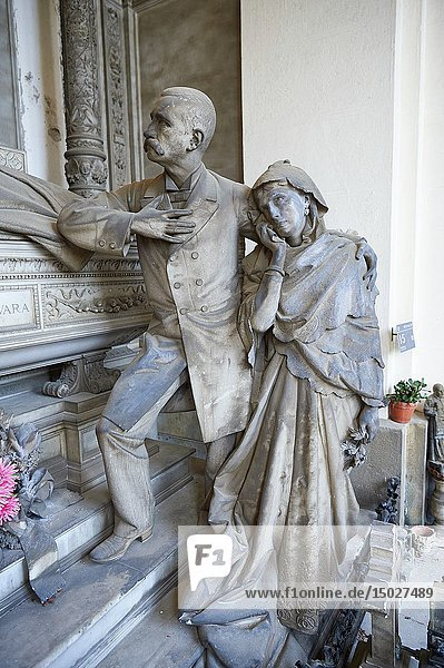 Picture and image of the stone sculpture of a grieving family around the death bed of the deceased. In a Borgeoise realistic style sculpted by GB Villa 1896. The Rivara Family Tomb  Section D no 15  the monumental tombs of the Staglieno Monumental Cemetery  Genoa  Italy.