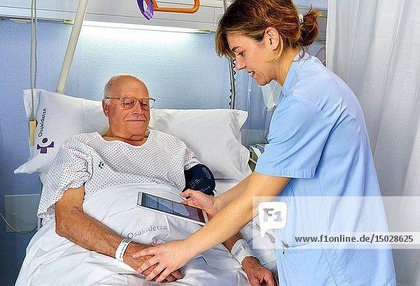 Nurse reading with the tablet the identification bracelet of a patient  hospital room  Hospital Donostia  San Sebastian  Gipuzkoa  Basque Country  Spain