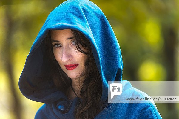 A beautiful 32 year old brunette woman wearing a hooded cape  outdoors.