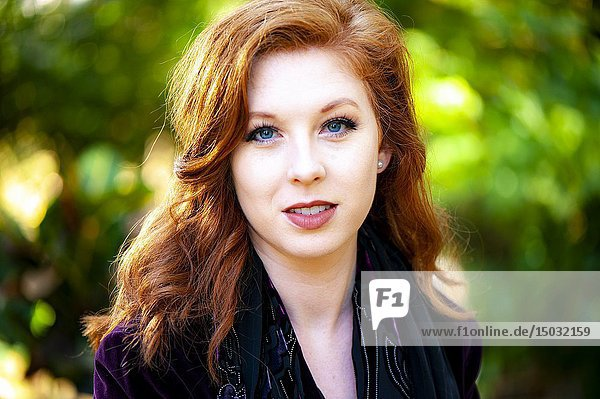 Portrait of a 25 year old redheaded woman in a garden setting.